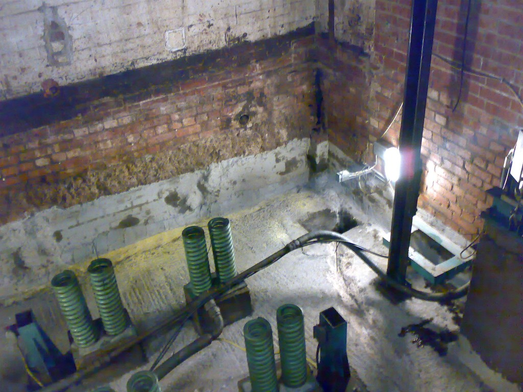 Lower section of walls and floor coated with waterproofing slurry