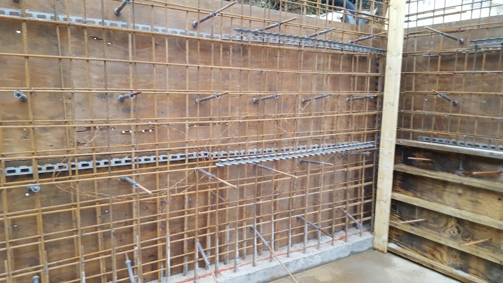 Walls reinforced with steel bars linked to steel coming through the kicker from the base