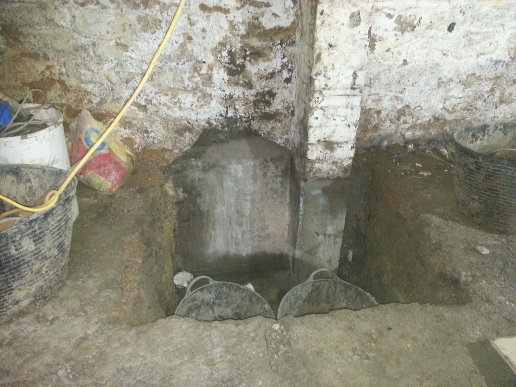 Underpinning in sections to lower the floor whilst supporting the building